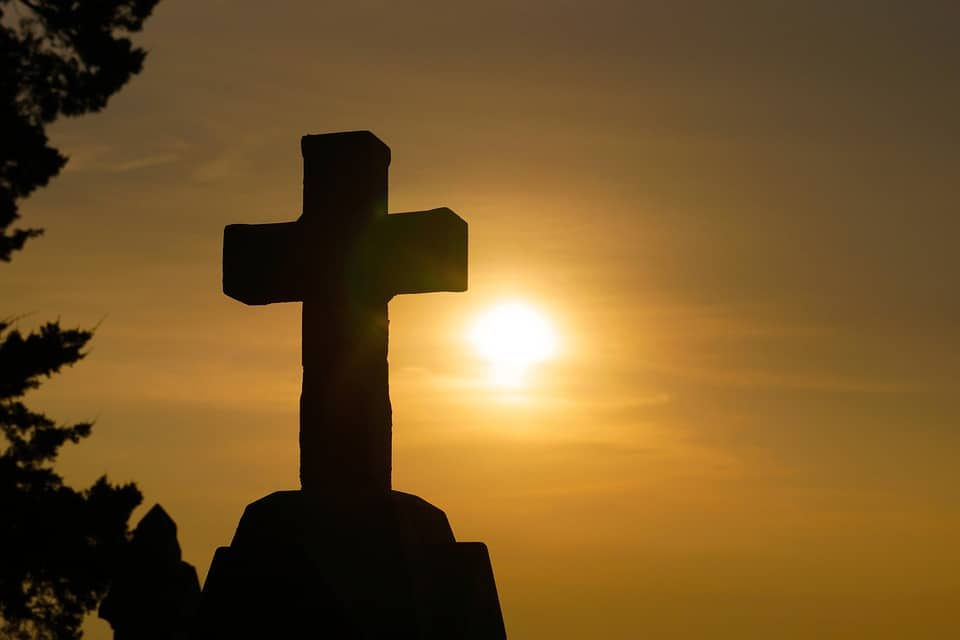 A picture of a cross with the sun behind it